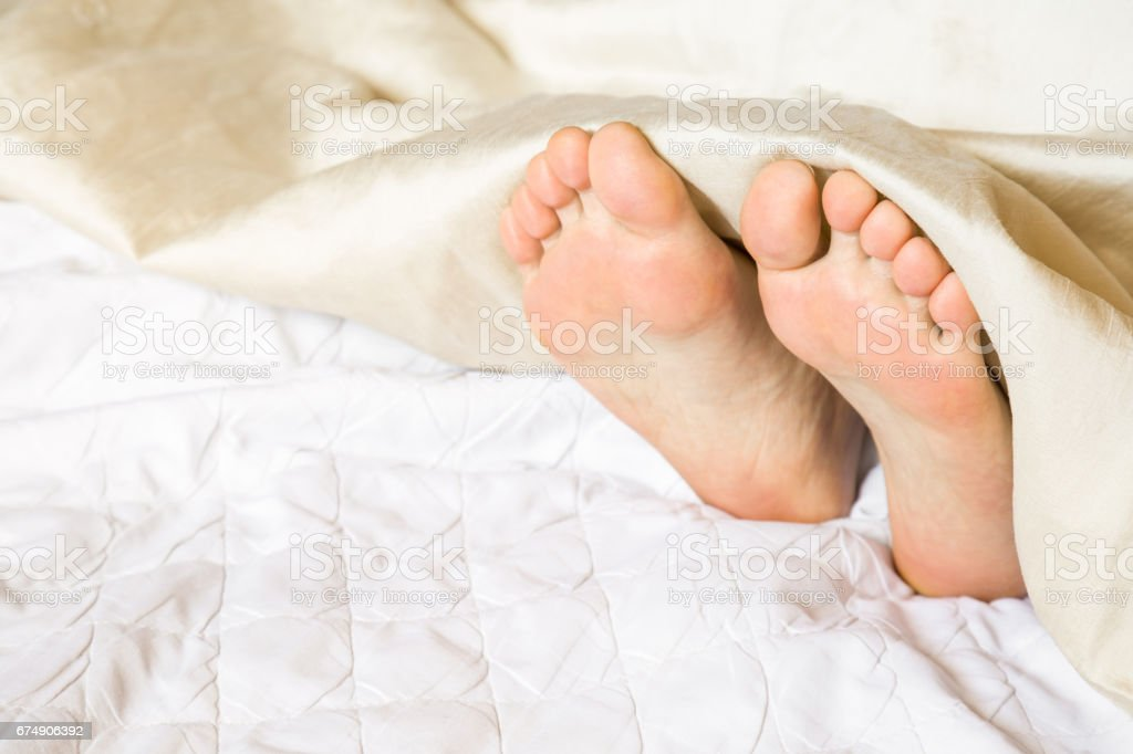 Young woman\'s feet sleeping almost under the blanket in the bed....