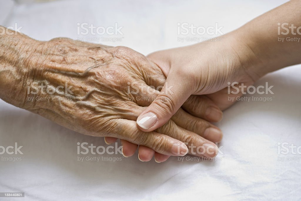 Young woman's hand holding the hand of a senior royalty-free stock photo