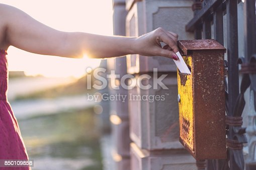 istock Young woman`s hand inserts a letter in mailbox 850109858