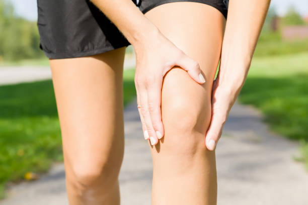 young woman's hand touching her knee during running time on footpath. joint pain. sporty problem and solution. close up. front view. - ginocchio foto e immagini stock