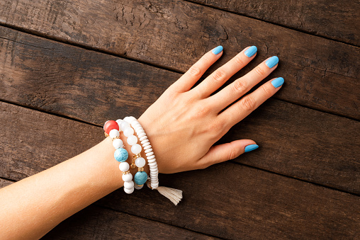 Young woman's hand with blue painted fingernails and bracelet. Top view