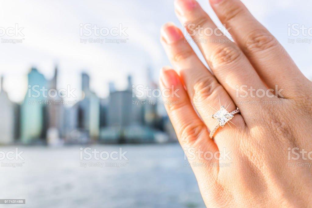 Corte de mão de mulher jovem com princesa de anel de noivado de diamante, ouro fora ao ar livre em NYC New York City Brooklyn Bridge Park pelo rio east, cityscape, horizonte bokeh - foto de acervo