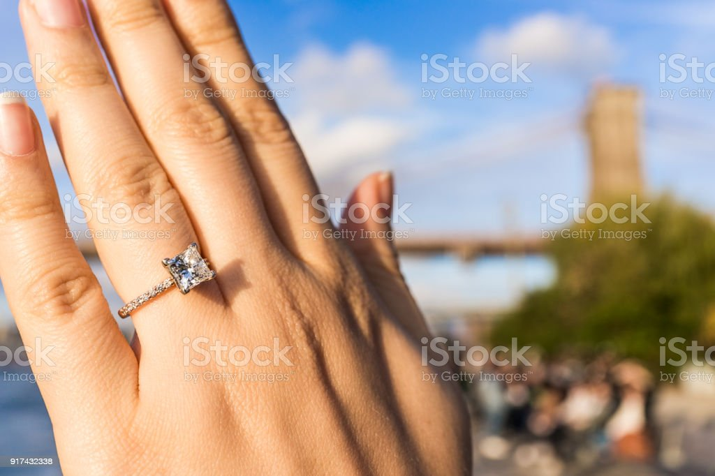 Young woman's hand with diamond engagement ring princess cut, gold outside outdoors in NYC New York City Brooklyn Bridge Park by east river, cityscape, skyline bokeh stock photo