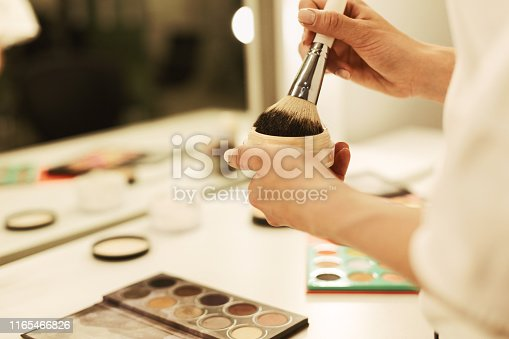 istock Young Woman's Hands Holding Makeup Brush And Powder Against Mirror 1165466826
