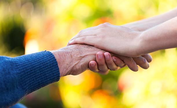 young woman's hands holding alter mann die hände - bettler stock-fotos und bilder