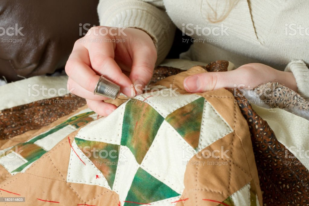 Young Woman's Hands with Thimble and Sewing Needle Quilting stock photo
