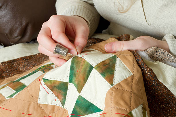young woman's hands with thimble and sewing needle quilting - quilt stock photos and pictures