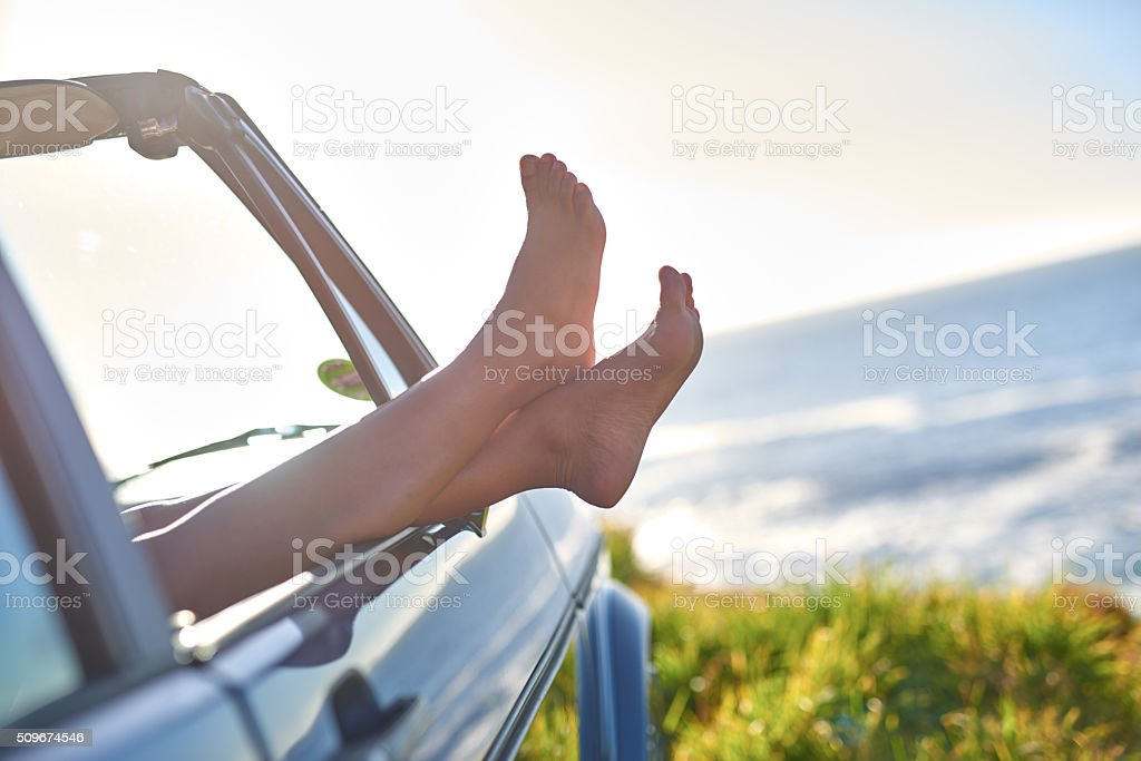 Young woman's legs sticking out the window during road trip stock photo