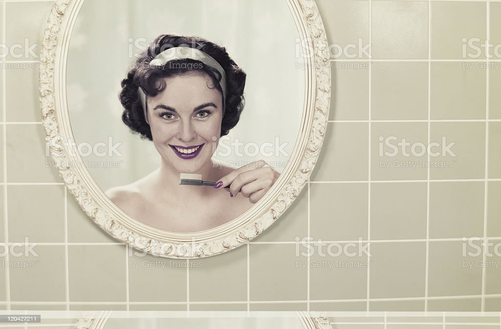 Young woman's reflection in mirror holding toothbrush, smiling, portrait royalty-free stock photo