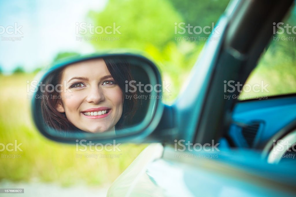 Young woman's reflection in side view mirror royalty-free stock photo