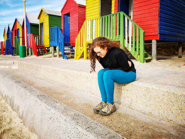 Young women afflicted with abdominal cramps after a jog Young women afflicted with abdominal cramps after a jog. Colorful beach huts ar in the background. taken on mobile device stock pictures, royalty-free photos & images
