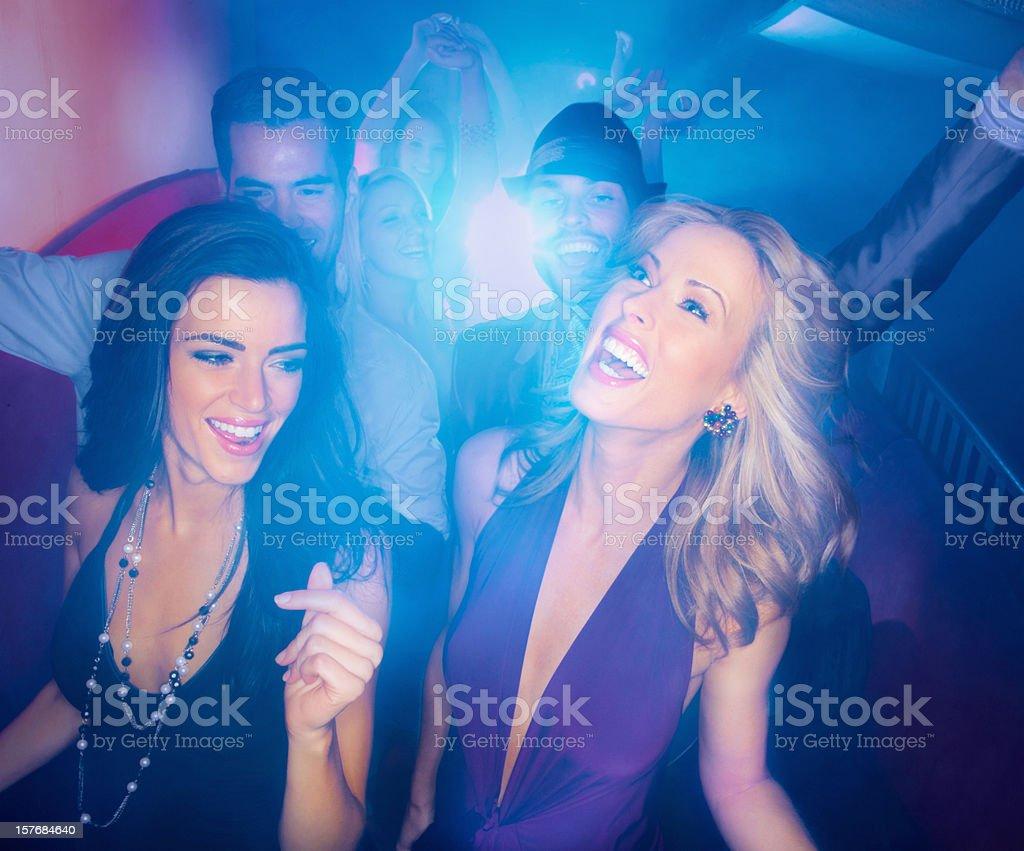 Young women and men enjoying in a nightclub royalty-free stock photo