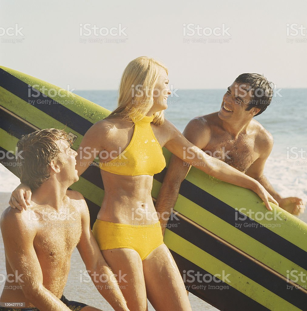 Young women and men with surfboard on beach, smiling royalty-free stock photo