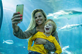 Young beauty women holding small boy and taking a photo  in aquarium