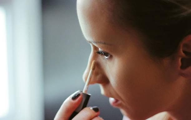 young women applied concealer under the eyes - poniżej zdjęcia i obrazy z banku zdjęć