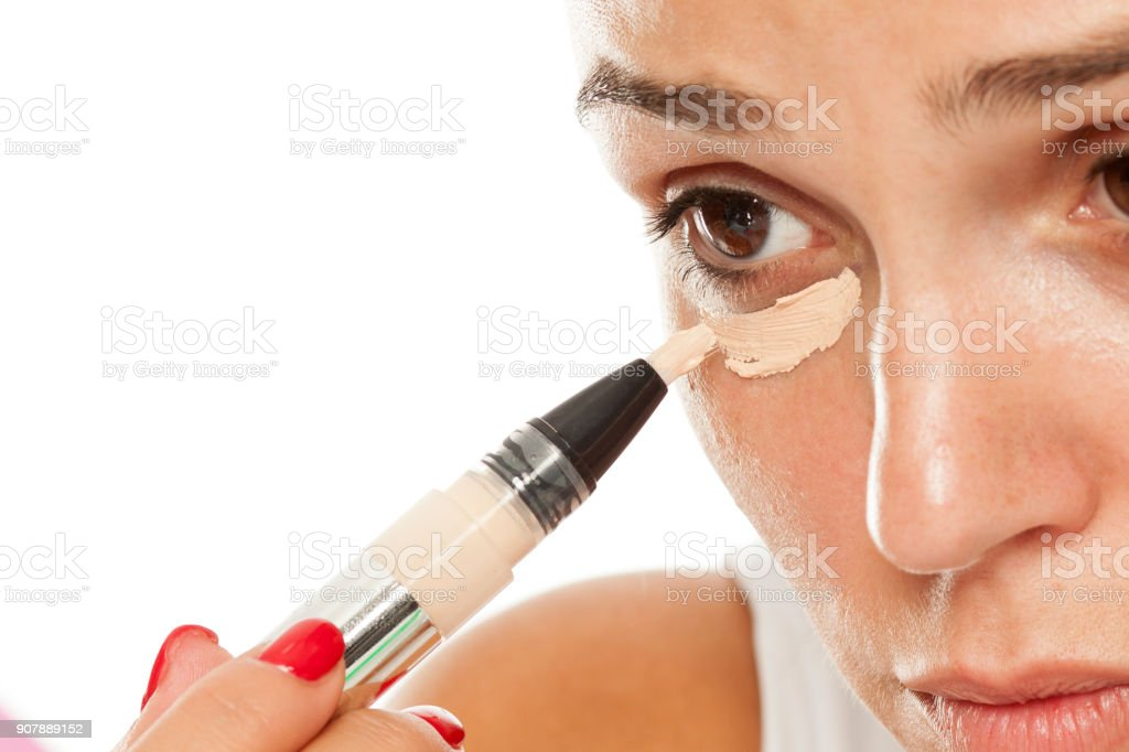 young women applied concealer under the eyes with applicator stock photo