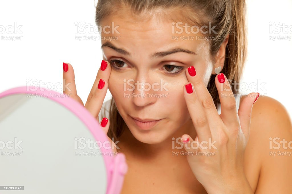 young women applied concealer under the eyes with her fingers stock photo