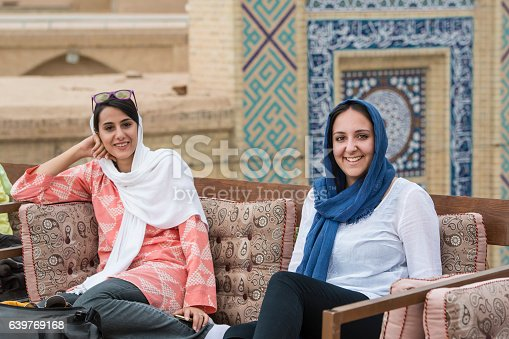Young female western tourist and her female iranian tourguide are sitting in a typical rooftop cafe in the town of Yazd, Iran. Both are wearing the typcial simple headscarf (hijab or rousari).