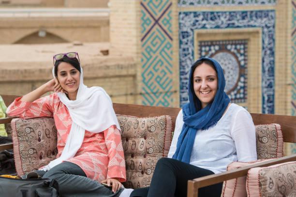 young women are sitting in a rooftop cafe, yazd. iran - iranische stock-fotos und bilder
