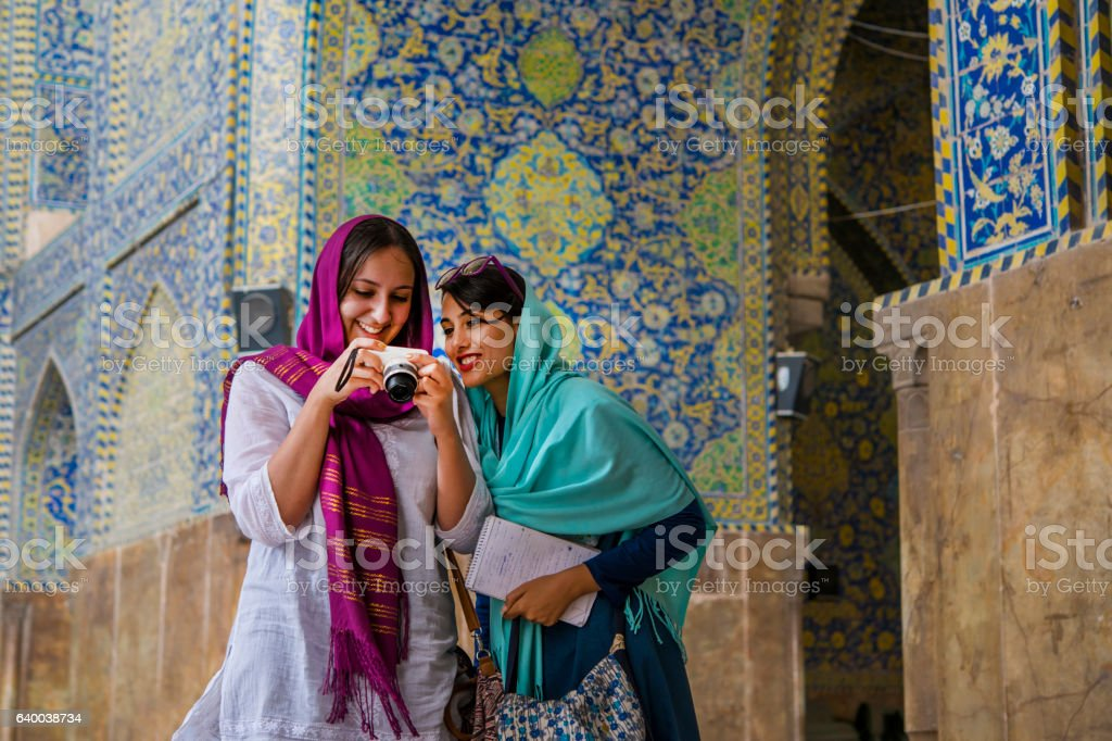 Young women are watching images at camera display, Isfahan, Iran stock photo
