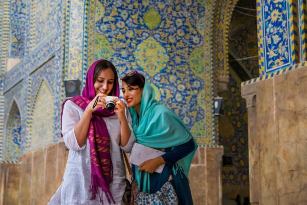 young women are watching images at camera display, isfahan, iran - iranische stock-fotos und bilder