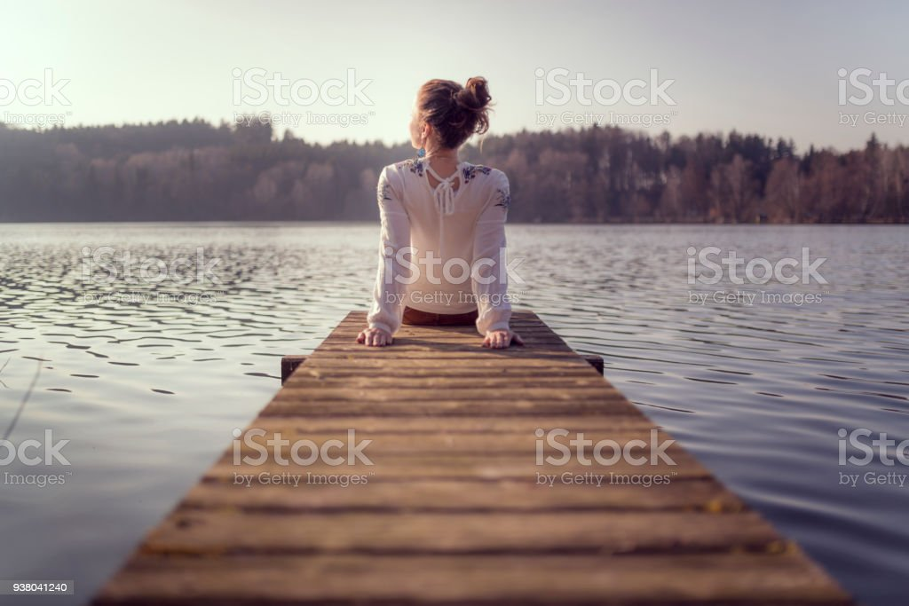 young women at a wooden pier on a lake in austria stock photo