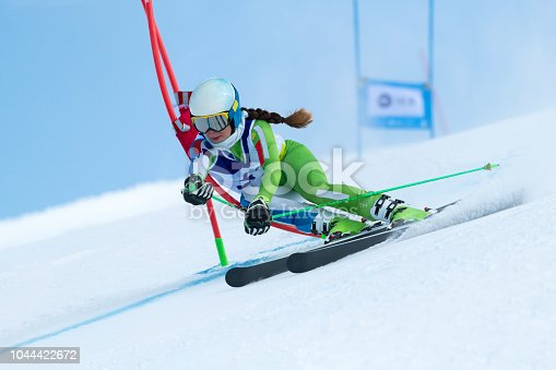 Front view of young female alpine skier at giant slalom