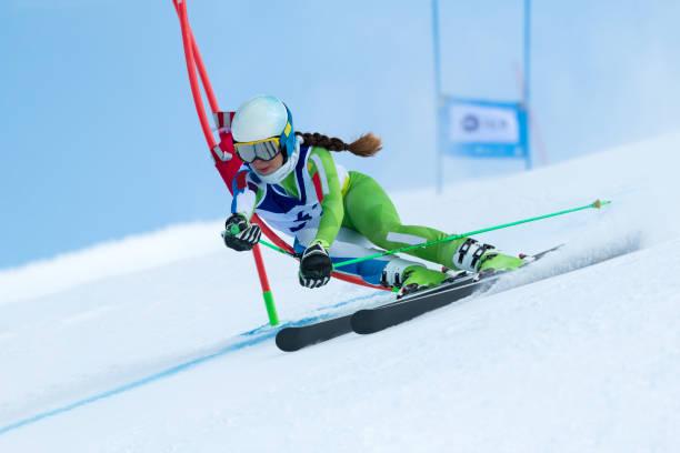 junge frauen beim riesenslalom gegen den blauen himmel - skirennen stock-fotos und bilder