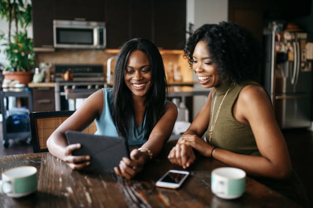 Young women at home, watching stuff on tablet together stock photo