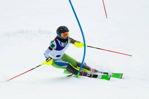 junge frauen im slalom ski, vorbei an der blauen tor - skirennen stock-fotos und bilder