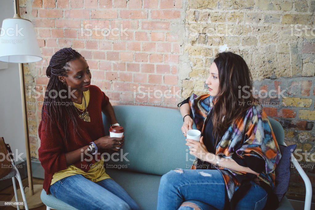 Portrait of a two young women of different ethnicities, sitting...