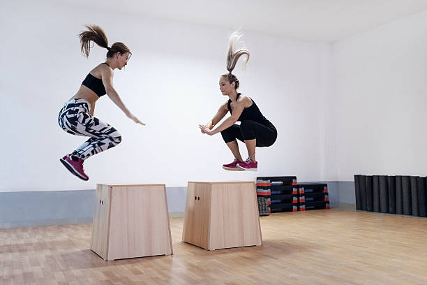 young women athletes doing box jump in the gym - boxen live stock-fotos und bilder