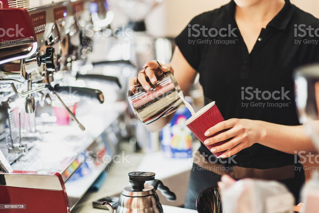Young women barista at work in a cafe. Preparing coffee stock photo