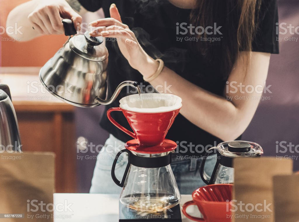 Young women barista at work in a cafe. Preparing pour over coffee stock photo