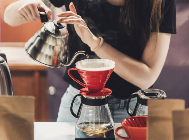 young women barista at work in a cafe. preparing pour over coffee - barista making coffee stock pictures, royalty-free photos & images