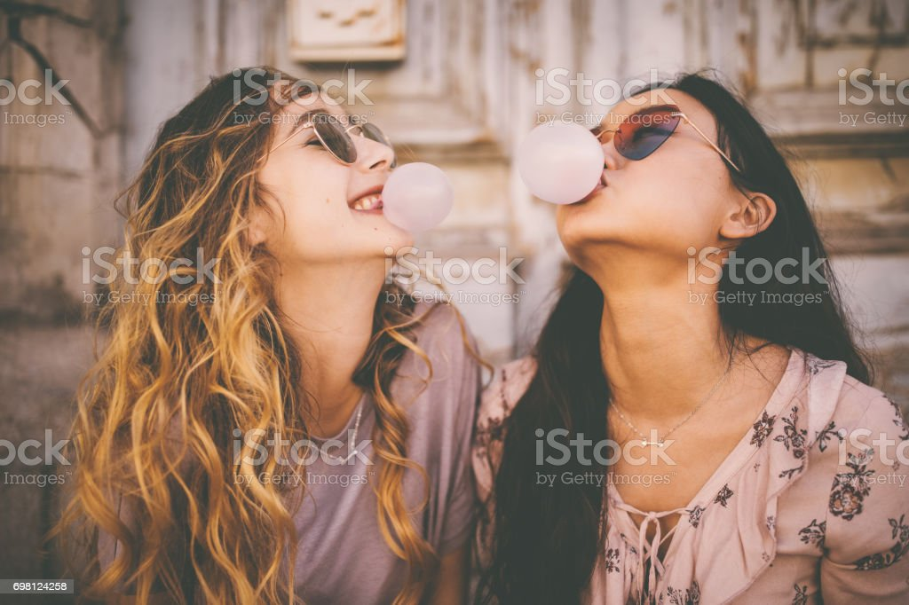 Young women blowing bubbles with bubble gum in urban setting