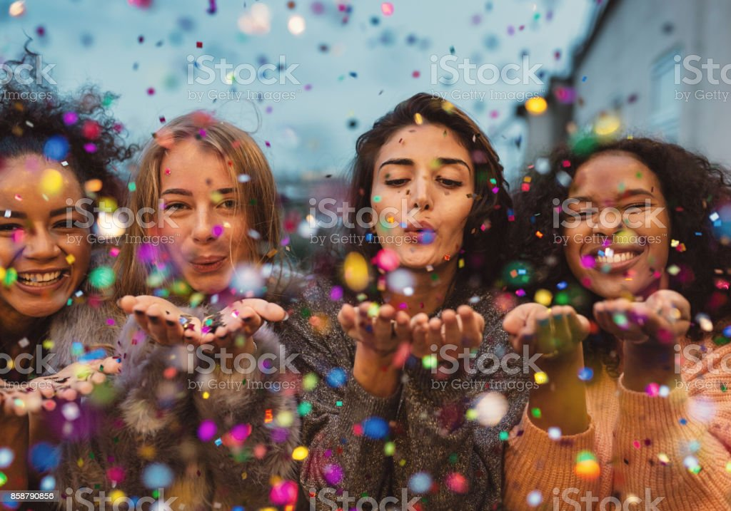 Young women blowing confetti from hands. royalty-free stock photo