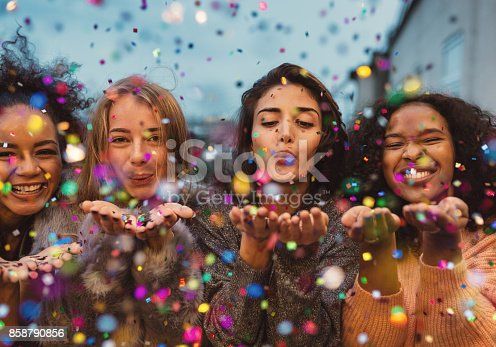 istock Young women blowing confetti from hands. 858790856