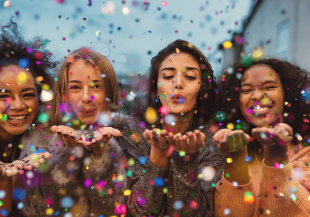 young women blowing confetti from hands. - millennial generation stock photos and pictures