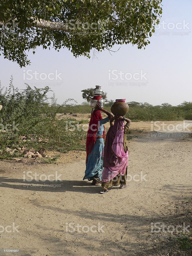 Young women bringing water from the lake in Rajasthan India royalty-free stock photo
