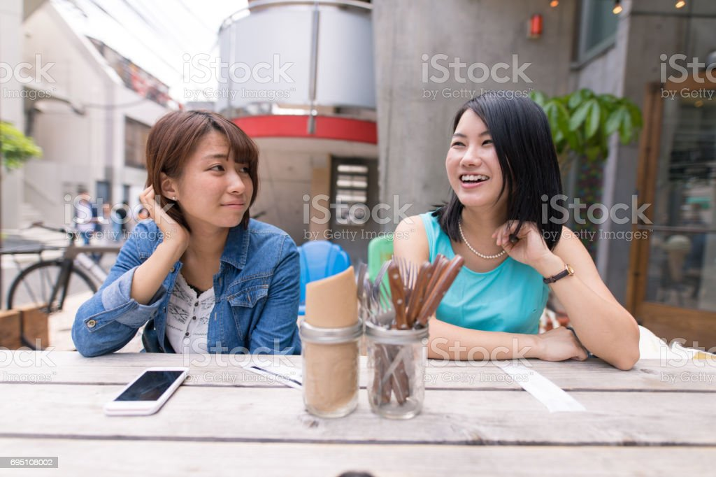 Young women casually talking at open cafe stock photo