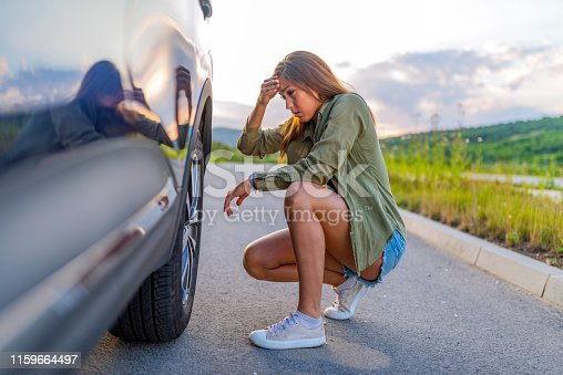 A young woman in the city with a flat tire, frustrated near the broken car. Woman changing a wheel after a car breakdown at the side of the road. Transportation