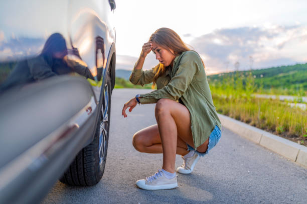 Young Women Changing A Flat Tire A young woman in the city with a flat tire, frustrated near the broken car. Woman changing a wheel after a car breakdown at the side of the road. Transportation aground stock pictures, royalty-free photos & images