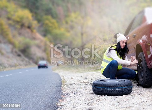 104275470istockphoto Young Women Changing A Flat Tire 909145484
