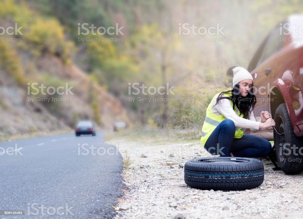 Young Women Changing A Flat Tire stock photo
