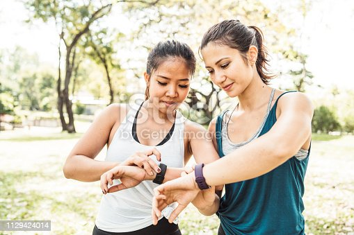 Young women checking their fitness trackers at the park