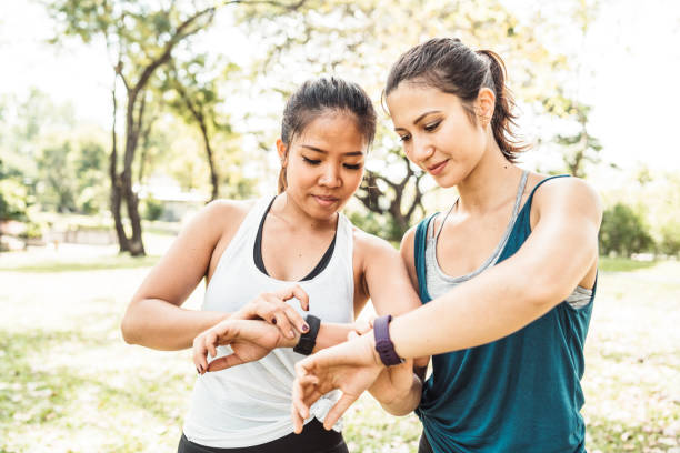 Young women checking their fitness trackers at the park Young women checking their fitness trackers at the park fitness tracker stock pictures, royalty-free photos & images