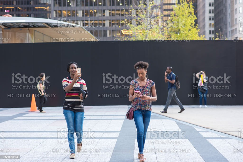 Young women checking their phones in Chicago stock photo