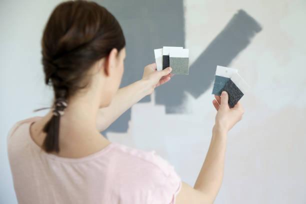 Junge Frauen wählen einen perfekten Grauton für Wände in ihrem neuen Zuhause – Foto