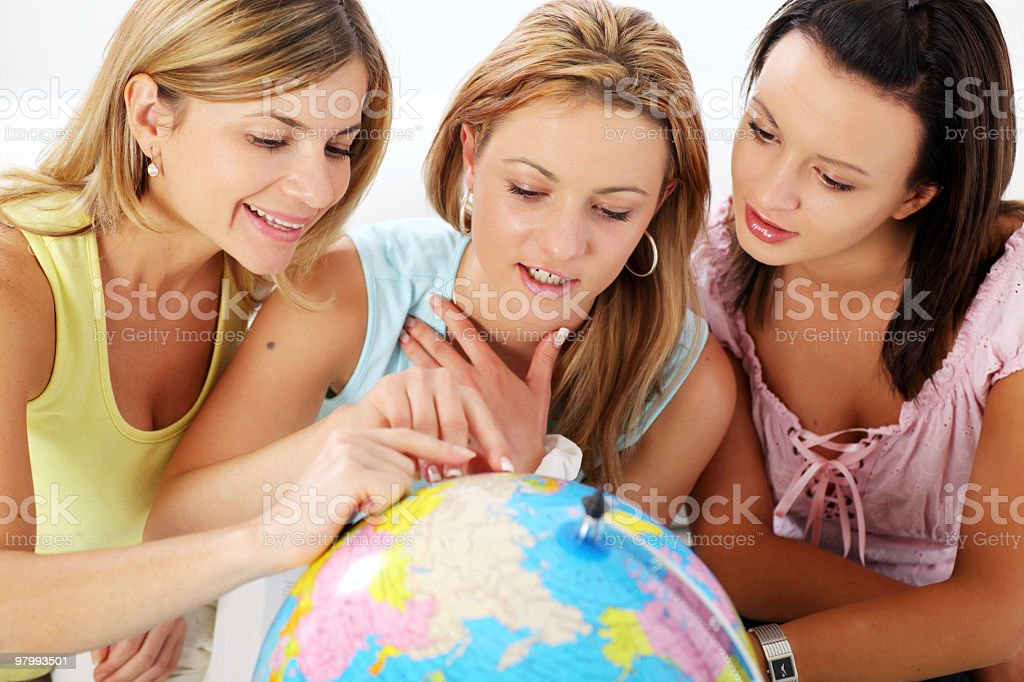 Young women choosing  travel destination on the globe. royalty free stockfoto